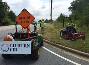 Workers cutting grass in right-of-way